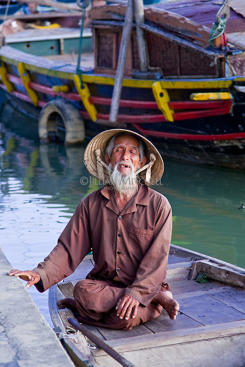 An old man with a long beard sitting on a small boat on the Thu Bon river in Hoi An.