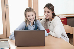 Portrait of schoolgirl and female childcare assistant looking at laptop