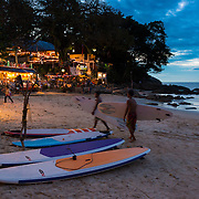 Surfers walking with surf boards at night to the rent shop on Kata beach, Phuket, Thailand