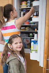 Sisters looking into refrigerator