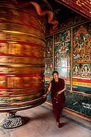 Monk pushing a huge prayer wheel at the entrace to a monastery near the Boudhanath Stupa, Kathmandu.
