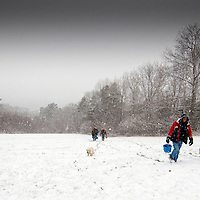 Local residents return from Damariscotta, Maine River at mean low tide harvesting fresh river oysters during a winter snow.