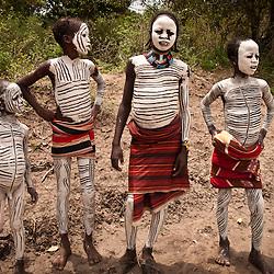 Children from the Karo tribe cover in full body paint.