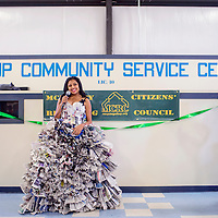 Maggie Robinson, right, takes a photo of Mercedes Mejia talks about her dress made of recycled newspapers during the annual Recycling Arts and Crafts Fair Saturday at the Gallup Community Service Center.