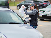 """26 MARCH 2020 - DES MOINES, IOWA: MARISSA BERGER, a special education teacher, delivers hot meals to people in a waiting car at Weeks Middle School. Des Moines Public Schools (DMPS) started distributing hot lunches Thursday, the first day students were supposed to return to school. Schools will now remain closed until 13 April. Meals were distributed with """"social distancing"""" in mind. On Thursday morning, 24 March, Iowa reported 175 confirmed cases of the Coronavirus (SARS-CoV-2) and COVID-19. Restaurants, bars, movie theaters, places that draw crowds are closed until 07 April. The Governor has not ordered """"shelter in place""""  but several Mayors, including the Mayor of Des Moines, have asked residents to stay in their homes for all but the essential needs. People are being encouraged to practice """"social distancing"""" and many businesses are requiring or encouraging employees to telecommute.        PHOTO BY JACK KURTZ"""