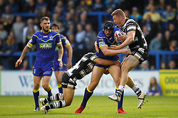 Warrington Wolves' Chris Hill is tackled by Hull FC's Danny Houghton (left) and Chris Green (right) during the Betfred Super League match at the Halliwell Jones Stadium, Warrington.