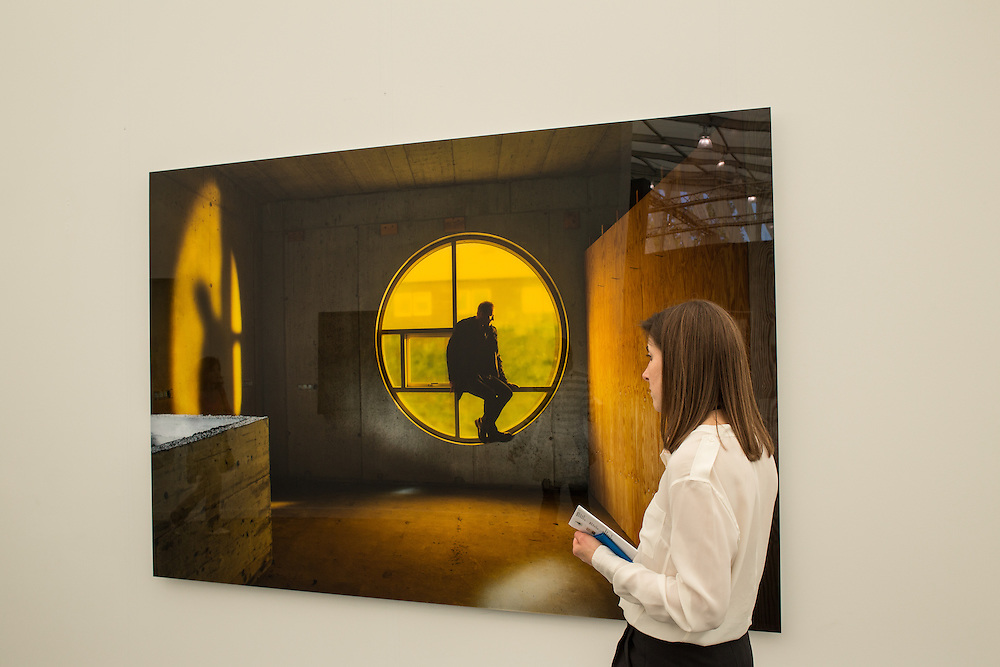 """A woman looks at Isaac Julian's photograph """"Midnight Sun"""" in the booth of Victoria Miro Gallery."""