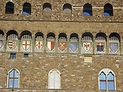 Detail from the Palazzo Vecchio. Town hall of Florence, Italy. A huge Romanesque fortress-palace overlooking the Piazza della Signoria. Designed by the architect Arnolfo di Cambio in 1299. This image shows the arches in the structure that are decorated with the 9 coats of arms of the Florentine Republic.