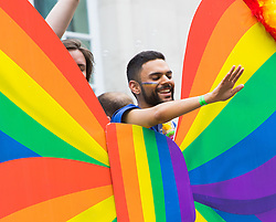 Portland Place, London, June 25th 2016. Thousands of LGBT people and their supporters gather for Pride in London, a colourful celebration of the hard-won rights of lesbian, gay, bisexual and transgender  people. PICTURED: A man waves to the crowd from the top deck of an open-topped bus.