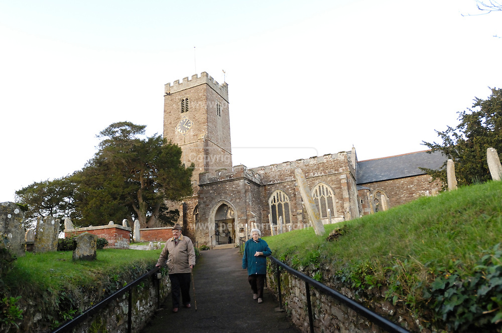 UK, November 24 2014:  Brian and Anne Horrell walk away from All Saints, East Budleigh church. Copyright 2014 Peter Horrell.