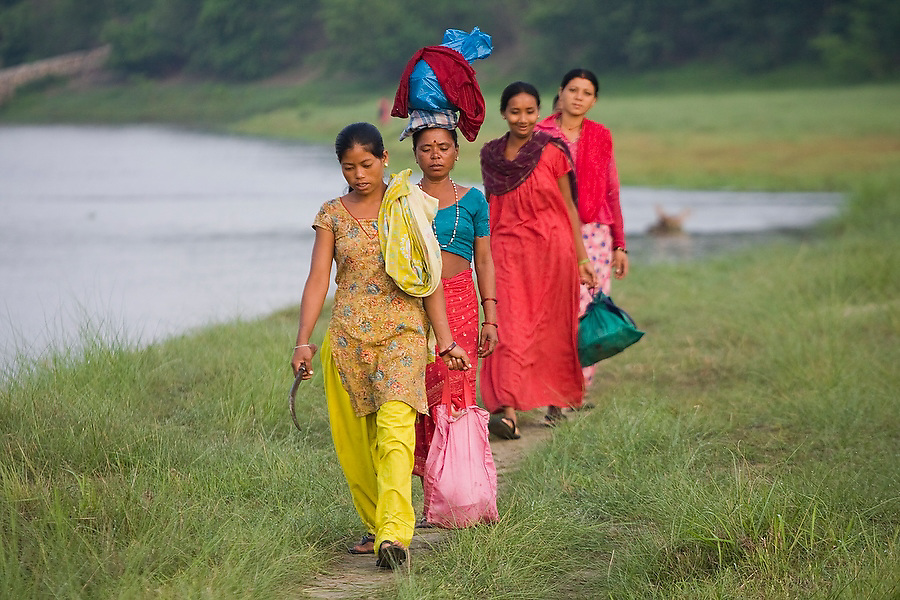 Village women head off to work in Royal Chitwan National Park, Terai, Nepal. The park employs large numbers of local villagers to clear small parts of the park for ecosystem management and easier wildlife viewing.