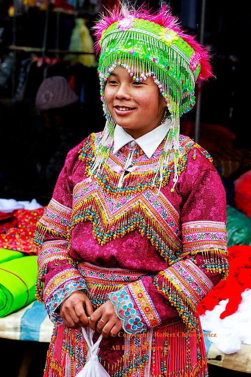 Lady of the Flower Hmong: A young lady stands in the colourful traditional clothing and head-dress of the Flower Hmong Tribe, with her purchase, in the morning market in Bac Ha Vietnam.