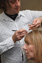 Hairdresser who has Ehlers-Danlos Syndrome (EDS), helped into employment by the Ready 4 Work team, Nottinghamshire County Council, styling and colouring a woman's hair