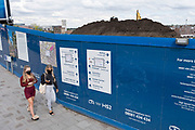 Young women wearing face masks pass the construction site hoardings for the HS2 mainline station at Curzon Street on 3rd August 2020 in Birmingham, England, United Kingdom. The Curzon Street Masterplan covers a 141 hectare area of regeneration, focussed on HS2 Curzon Street station in Birmingham city centre, combined with approximately 700 million in investment into the surrounding area including new homes and commercial developments. High Speed 2 is a partly planned high speed railway in the United Kingdom with its first phase in the early stages of construction, the second phase is yet to receive full approval and the third is subject to merging with Northern Powerhouse Rail, a separate project.