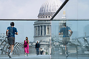 With the dome of St Paul's cathedral in the distance, a woman in a crimson dress crosses the river Thames on the Millennium Bridge, on 24th June 2021, in London, England. London's newest river crossing for 100-plus years coincided with the Millennium. It was hurriedly finished and opened to the public on 10 June 2000 when an estimated 100,000 people crossed it to discover the structure oscillated so much that it was forced to close 2 days later. Over the next 18 months designers added dampeners to stop its wobble but it already symbolised what was embarrassing and failing in British pride. Now the British Standard code of bridge loading has been updated to cover the swaying phenomenon, referred to as 'Synchronous Lateral Excitation'. CREDIT RICHARD BAKER.