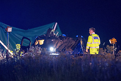 © Licensed to London News Pictures . 21/07/2014 . Nottinghamshire , UK . A police officer looks at an overturned car at the scene . Police , fire crew and ambulances on the A1 road in Ranby yesterday morning (21st July 2014) following a fatal multi vehicle accident . Leroy and Sheila Carrington (aged 68 and 58) died at the scene when the Peugot 206 they were driving collided with a Vauxhall Astra . Roderick Franks (58) , who was a passenger in the Astra , died in hospital , following the crash . The road was closed in both directions whilst police investigated the scene .  Photo credit : Joel Goodman/LNP