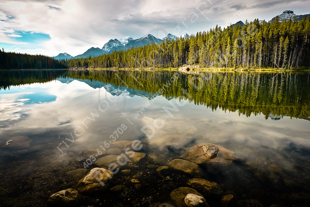 The reflection of the Bow Range in the glassy calm waters of Herbert Lake. Herbert is a beautiful little lake at the Southern end of the Icefields Parkway. It is often missed by tourists because of it's size, but it is definitely worth stopping for...©2010, Sean Phillips.http://www.RiverwoodPhotography.com