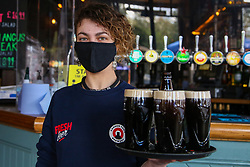 © Licensed to London News Pictures. 12/04/2021. London, UK. A bar maid holds a tray with glasses of Guinness at The Finsbury Pub, in Hackney, north London, which reopens after 4 months of Covid-19 lockdown. Cafes, restaurants, pubs, non-retail business and hairdressers across the UK closed following third national lockdown on 6 January, after a surge of coronavirus infections and hospital admissions across the UK. As restrictions are eased, cafes, restaurants, pubs, non-retail business and hairdressers reopen today.<br /> Photo credit: Dinendra Haria/LNP