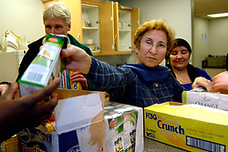 Volunteers give out free food past its sell by date for refugees and asylum seekers in a soup kitchen at a church hall; Bradford Yorkshire UK