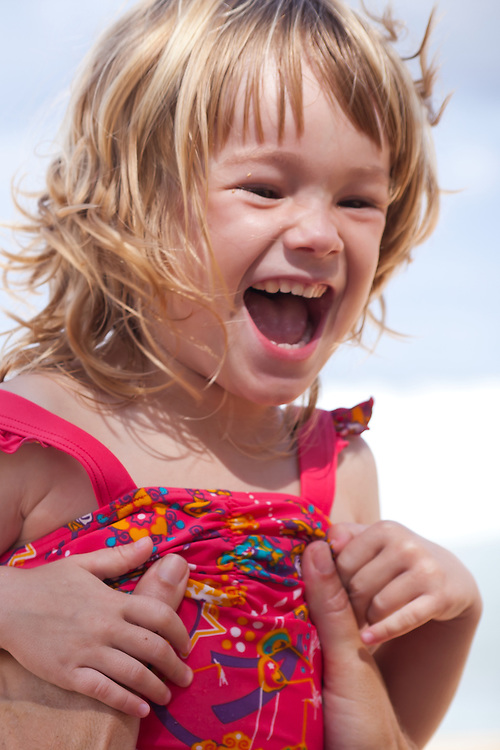 A little girl laughs in delight at her father on the beach in Hawaii