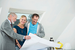 Architect and couple with construction plan at construction site of new building