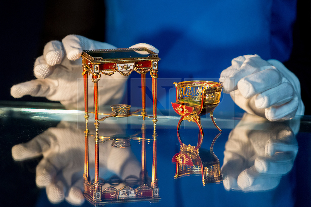 """© Licensed to London News Pictures. 31/05/2019. LONDON, UK. A staff member presents """"A fine and rare Fabergé gold and enamel miniature bonbonnière chair"""" by workmaster Michael Perchin, circa 1900, and """"A fine and rare Fabergé vari-colored gold, guilloché enamel and nephrite miniature table bonbonnière"""" by workmaster Michael Perchin, 1899-1908, (Est: £800,000 – 1.2 million) at a preview of works from the upcoming sale of Russian Pictures, Works of Art, Fabergé & Icons Sales at Sotheby's, New Bond Street, on 4 June 2019.  Photo credit: Stephen Chung/LNP"""