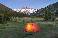 Tent illuminated at dusk in backcountry camp, Eagle Cap Wilderness Oregon
