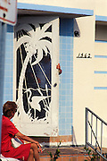 Classic Miami Beach: an older couple and a vintage screen door on a 1937 Art Deco apartment building designed by Henry Hohauser. Since this photo was made in the early 1990s, this remarkable screen door was removed from the building and is now presumed lost.