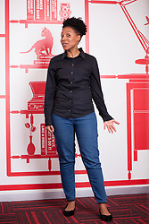 CAPE TOWN, SOUTH AFRICA,MAY 24, 2017. A young coloured woman holds out her hand in a fun gesture.She's wearing a black blouse and blue jeans as she stands in front of red and white graphic wallpaper. (Picture: JULIAN GOLDSWAIN)