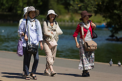 © Licensed to London News Pictures. 22/07/2014. London, UK. Women in floppy sun hats walk past the a lake enjoying the sunshine in Regents Park in central London this lunchtime. Photo credit : Vickie Flores/LNP