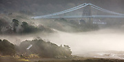 """""""An eary morning fog rolls in off the sea, shrouding the idyllic church and graveyard of Ynys St Tysilio, Anglesey.<br /> <br /> The 100 foot high Menai Suspension Bridge, completed in 1826 by Sir Thomas Telford, looms above the sea fog which burned off by mid-morning"""