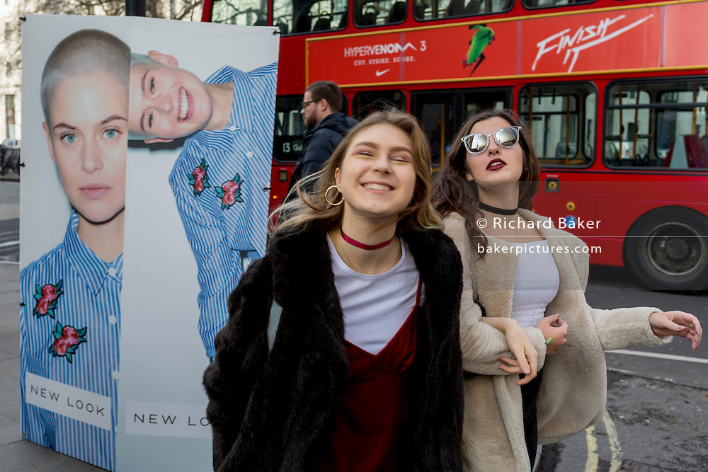 """Models have fun next to a street billboard for high-street retailer New Look, outisde London Fashion Week in the Strand, on 17th Febriary 2017, in London, England, United Kingdom. London Fashion Week is a clothing trade show held in London twice each year, in February and September. It is one of the """"Big Four"""" fashion weeks, along with the New York, Milan and Paris. The fashion sector plays a significant role in the UK economy with London Fashion Week alone estimated to rake in £269 million each season. The six-day industry event allows designers to show their collections to buyers, journalists and celebrities and also maintains the city's status as a top fashion capital. (Photo by Richard Baker / In Pictures via Getty Images)"""