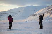 UNIS student Kiya Riverman poses on sea ice in Templefjorden, Svalbard as classmate Alia Khan takes her picture.