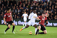 Wilfried Bony of Swansea city is tackled by Richard Dunne of QPR. Barclays Premier league match, Swansea city v Queens Park Rangers at the Liberty stadium in Swansea, South Wales on Tuesday 2nd December 2014<br /> pic by Andrew Orchard, Andrew Orchard sports photography.
