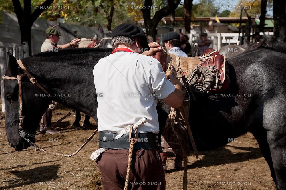 GAUCHO PREPARA LA MONTURA AL CABALLO, FERIA ESPECIAL EN CARMEN DE ARECO, PROVINCIA DE BUENOS AIRES, ARGENTINA