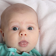 A two month old baby girl in a bedroom setting makes eye contact with the camera. Photo Tim Clayton