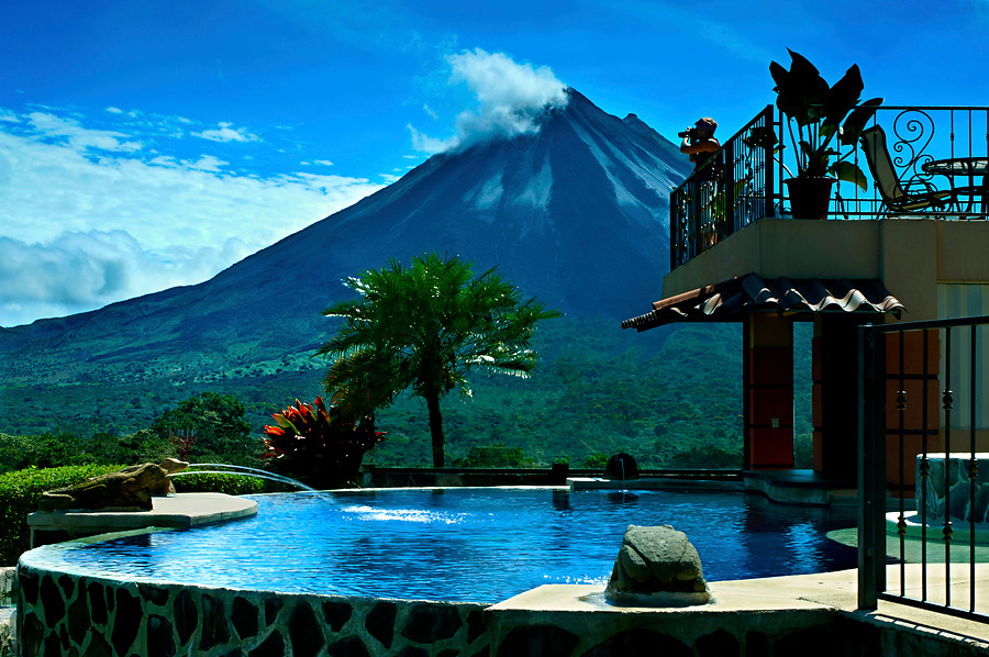The very active Arenal Volcano provides a dramatic backdrop for a tourist enjoying the views from her mountain lodge.