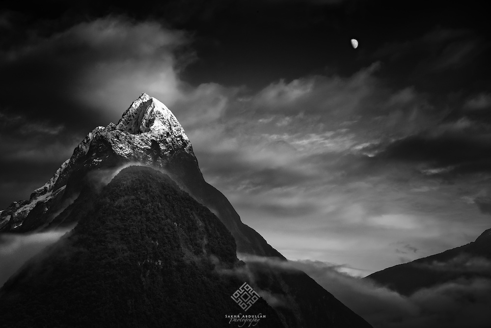 At lovely morning, sunrise mingled with moonset in a majestic scenery of Milford Sound peaks.