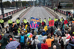 © Licensed to London News Pictures. 07/10/2019. London, UK. Police block Extinction Rebellion activists from crossing Lambeth Bridge in central London . Activists will converge on Westminster blockading roads in the area for at least two weeks calling on government departments to 'Tell the Truth' about what they are doing to tackle the Emergency. Photo credit: Peter Macdiarmid/LNP