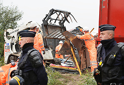 """French police officers stand guard as a large crew of demolition workers start breaking down living areas of the """"Jungle"""" migrant camp, close to Calais in northern France."""