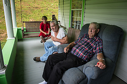 Hershel Aleshire (right) of Blair, West Virginia which is in the heart of the Appalacian mountains, sits outside his home with his friend, Carlos Gore and ?.. He is in the heart of America where mountaintop-removal mines are abundant. Mountaintop Removal is a method of surface mining that literally removes the tops of mountains to get to the coal seams beneath. It is the most profitable mining technique available because it is performed quickly, cheaply and comes with hefty economic benefits for the mining companies, most of which are located out of state. Many argue that they have brought wage-paying jobs and modern amenities to Appalachia, but others say they have only demolished an estimated 1.4 million acres of forested hills, buried an estimated 2,000 miles of streams, poisoned drinking water, and wiped whole towns from the map. The mountaintop-removal mine near Blair caused the population to fall from 700 in the 1990s to fewer than 50 today, according to the Blair Mountain Heritage Alliance. © Ami Vitale