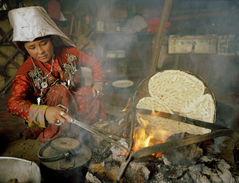 """Pegich, young wife of Er Ali Boi (married 2 years), the richest  """"sane"""" man in Pamir, bakes bread. Er Ali Boi is one of the rare Kyrgyz to spend winter in a yurt."""