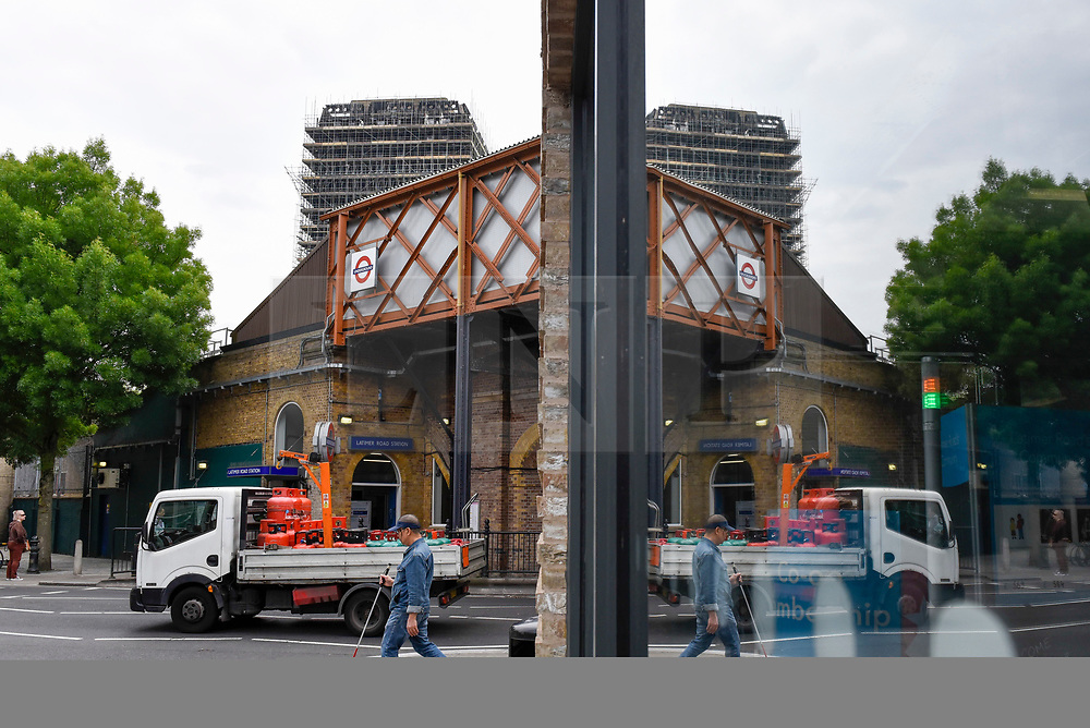 © Licensed to London News Pictures. 21/05/2018. LONDON, UK.  The burned out shell of the Grenfell Tower, currently covered in scaffolding, looks down over Latimer Road tube station in West London on the day that commemoration hearings begin in the Millennium Gloucester hotel.  Over the next nine days, friends and family will be paying tributes to the 72 victims killed by the fire in the building nearly one year ago.  Photo credit: Stephen Chung/LNP