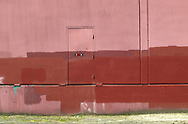 """Image of the back of a building with a somewhat creative paint job with a bumper stick emphasising the """"Art"""" in Earth."""