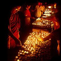 KATHMANDU, NEPAL. Tibetan Buddhist monk lights yak butter lamps during full moon ceremony at Bodhnath Stupa.