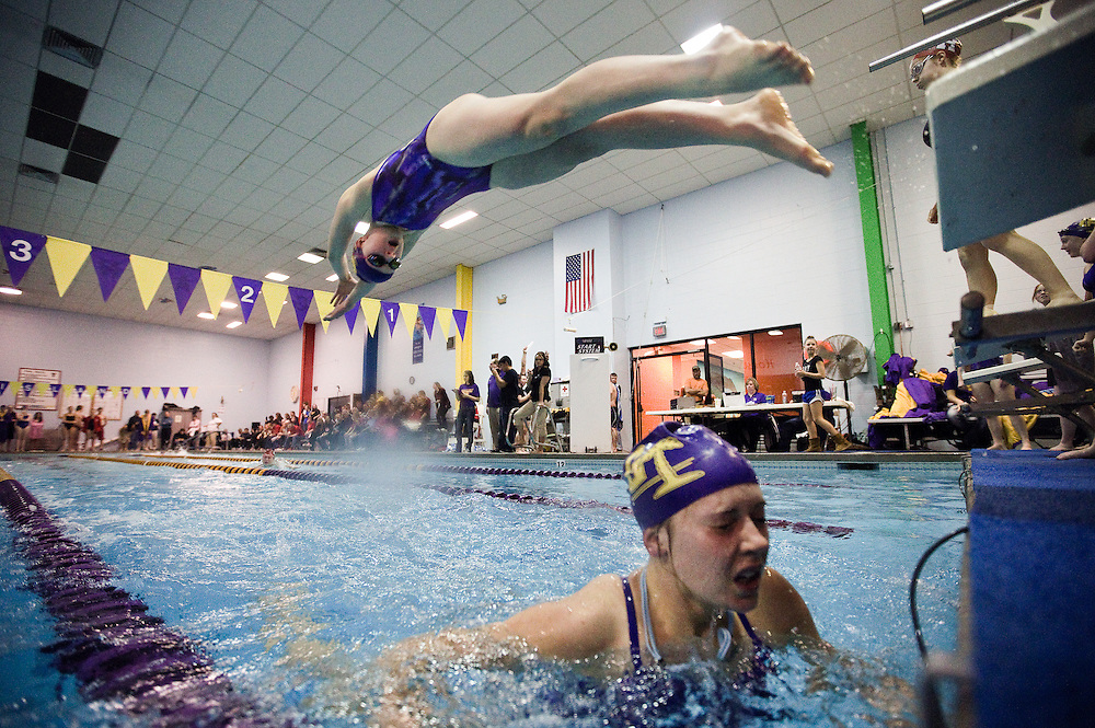 Grand Island's Sienna Kunze dives into the pool as Alyssa Fisher exits while competing in the 200 meter freestyle relay during Thursday's meet against Lincoln High at the Grand Island YMCA. (Independent/Matt Dixon)