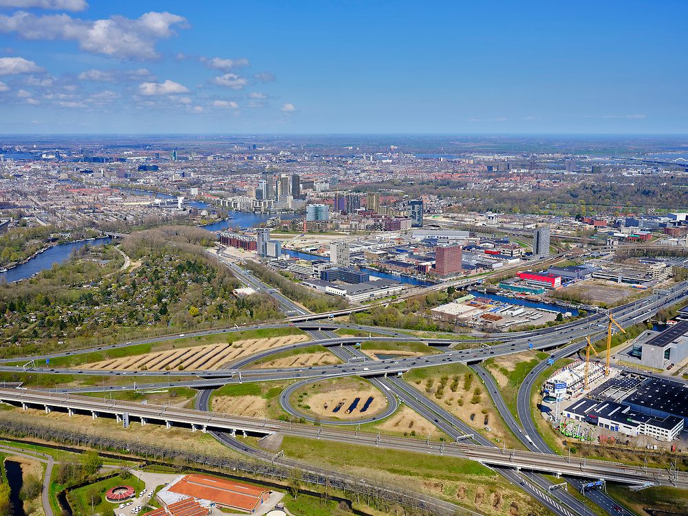 Nederland, Noord-Holland, Amsterdam; 16-04-2021; Knooppunt Amstel, Ring A10 en A2 gezien naar Utrechtsebrug. Links volktuinencomplex Amstelglorie, rechts Bedrijvenpark Zuidpark. <br /> Amstel junction, Ring A10 and A2 (to the right towards Utrecht).<br /> On the left allotment garden complex Amstelglorie, adjacent to Zuidpark Business Park.<br /> <br /> luchtfoto (toeslag op standard tarieven);<br /> aerial photo (additional fee required)<br /> copyright © 2021 foto/photo Siebe Swart