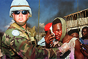 A US Army soldier assigned to the UN Force in Haiti aids a Haitian civilian who was beat up by a mob at a roadblock of burning tires on Harry Truman Blvd in the port area of Port au Prince, Haiti, Monday, Feb. 12, 1996. Haiti will install newly elected president Rene Preval in a ceremony Wednesday. This will be the first peaceful transition of power in Haiti's history. .PHOTO BY JACK KURTZ
