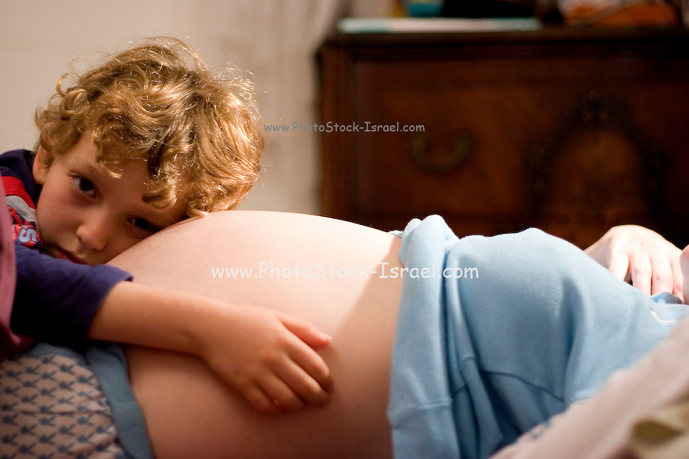 A young blond boy hugging his pregnant mother