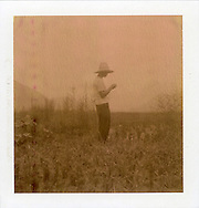 Polaroid chocolate portrait of a farmer in his field. He's wearing a hat and stands in middle of a field. Guangxi province, China, Asia.